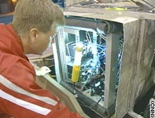 Student Scott Wilson checks some of CajunBot's electronics.